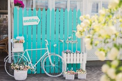 Photo zone for guests at wedding reception. White vintage bicycle, turquoise background, wooden 'wedding' pointer, flowers in baskets, 'dream' sign.