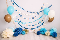 Photo zone with paper garlands, balloons, paper honeycombs, paper balls, pom poms and confetti.  Photo zone for birthday party and smash cake.  Blue, brown, gold, beige, turquoise colors.