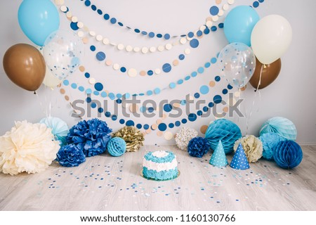 Photo zone with paper garlands, balloons, paper honeycombs, paper balls, pom poms, confetti and cream cake. Birthday cake. Smash cake. One year. Blue, brown, gold, beige, turquoise colors.