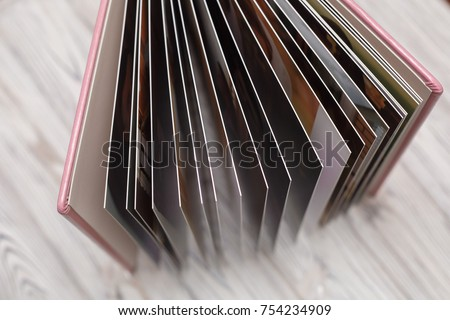 photobook with a hard cover on a wooden surface pink photo album with leatherette with a shield Expanded photo book pages open photo album