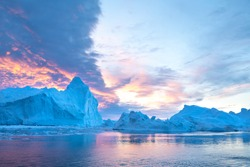 Photogenic and intricate iceberg under an interesting and colorful sky during sunset. Disko bay, Greenland.