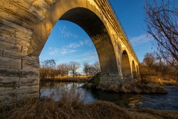 Photograph during golden hour of a historic five arch bridge across the Turtle Creek in southern Wisconsin