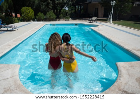 Photograph from behind of a couple of women entering a swimming pool with affectionate attitude