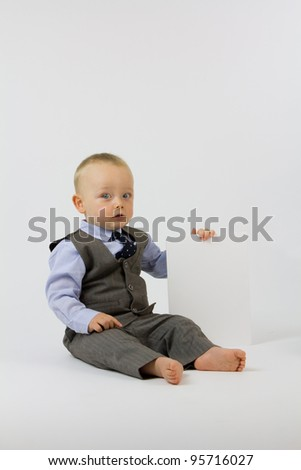 Photograph of a baby dressed smartly in business clothing whilst holding a blank piece of card, shot against white. - stock photo