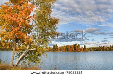 Photograph of a beautiful northwoods lake surrounded by the colors of autumn and blanketed by a wonderful october sky.