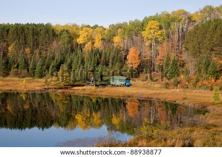 Photograph of a beautiful still northwoods lake with a small cabin surrounded by autumn colors.