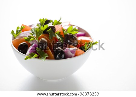 Photograph of a bowl of greek salad isolated on white