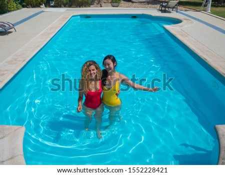 Photograph of a caucasian and chinese women entering a swimming pool with affectionate attitude