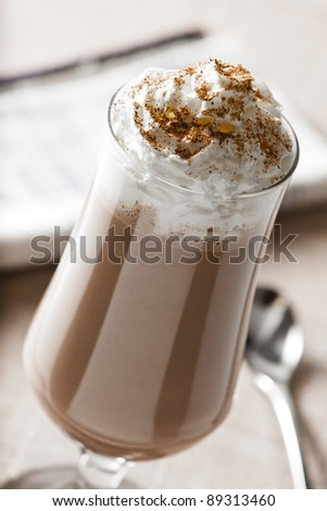 Photograph of a Chocolate Milk Shake with Whipped Cream and Cinnamon