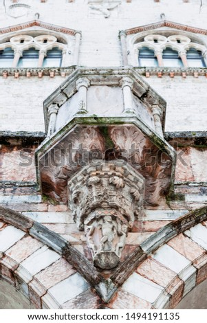 Photograph of a detail of the external facade of the Sala dei Notari, in Perugia, where you can see the colors and details of the sculpture.