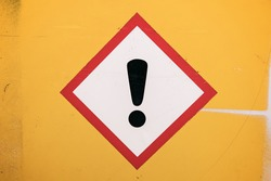 Photograph of a generic real diamond warning label against a bright yellow wall.