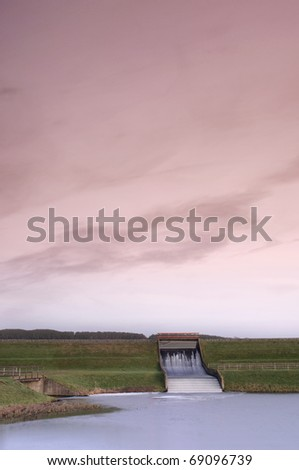 Photograph of a hydroelectric dam as it drains from a reservoir into a lower watercourse. Taken against a pink evening sky at sunset. Includes copyspace.