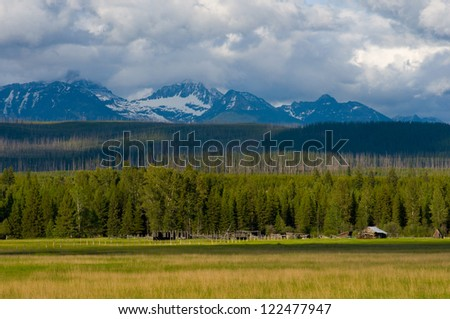 Photograph of a mountain scene with old rustic barn amidst a prairie setting in the foreground and the majestic peaks of Glacier National Park in the background.