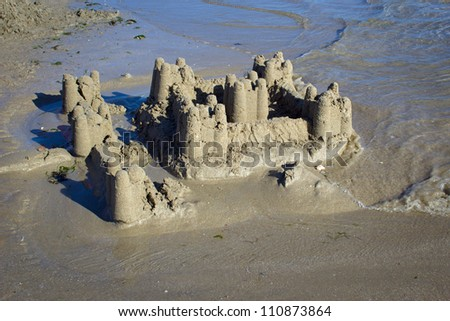 photograph of a sand castle collapsing by the tide on the coast of Brittany