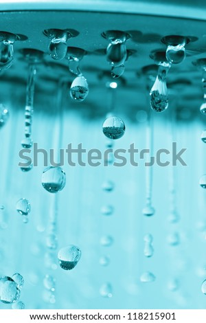 Photograph of a shower head showing drops and streams of water. Blue toned.