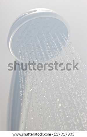 Photograph of a shower head showing drops with streams of hot water. Black and white photo taken in steam
