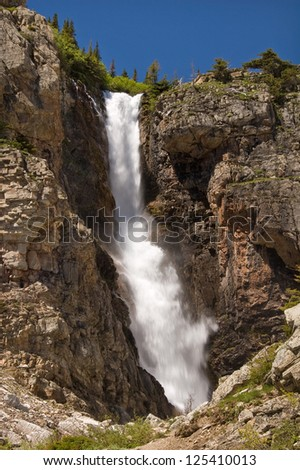 Photograph of a tall and beautiful waterfall high in the mountains of Glacier National Park in northwest Montana.