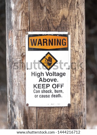 Photograph of a warning high voltage above sign informing people to keep off due to dangers including shock, burn, or death posted on a weathered wood pole or post in a rural area.