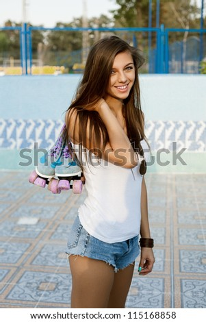 Photograph of a woman holding her roller skates by the laces, outdoors