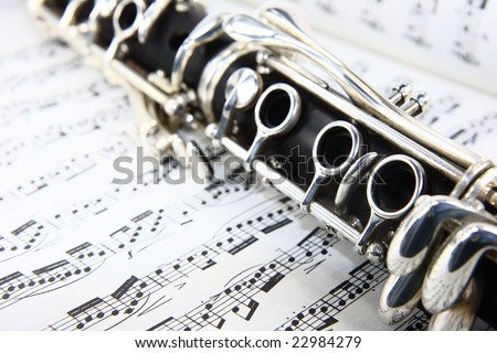 Photograph of a wooden clarinet over some music.