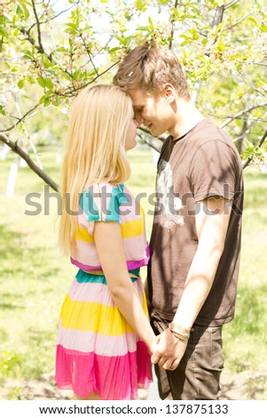 Photograph of a young romantic couple holding hands and coming too close to each other in the park.