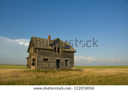 Photograph of an abandoned, weathered home found standing on the flatland of a North Dakota prairie.