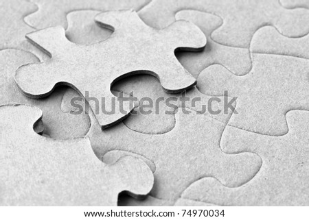 Photograph of blank grey cardboard jigsaw puzzle with two floating pieces on top, great material details.