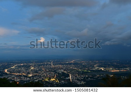 Photograph of Chiang Mai city in evening time with clouds and twilight sky.