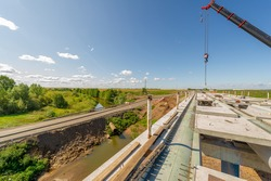Photograph of engineering structures. Construction of a road bridge over a river