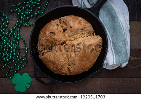 Photograph of Irish Soda Bread baked in a cast iron skillet for Saint Patrick's Day with Shamrock Beads Сток-фото ©