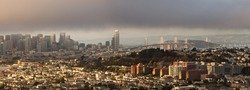 Photograph of San Francisco, including downtown skyline and the Bay Bridge, on foggy sunset.  Taken from Bernal Heights Park.