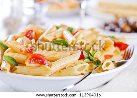 Photograph of some fresh pasta with tomato peppers and basil