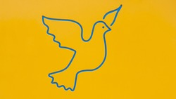 Photograph of the silhouette of the drawing of a flying bird in blue color on a yellow background