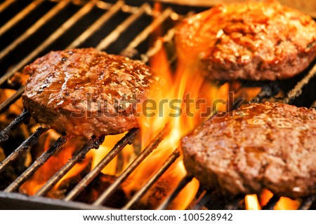 Photograph of three tasty beef burgers on the grill