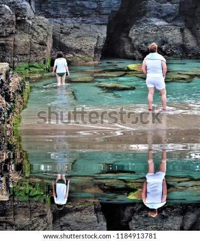 photograph of tourists climbing on the rocks and arch on the beach of the cathedrals, reflected in the water,tourism, tourist, advertising, tourist destination, holidays, travel, travelers, happiness, #1184913781
