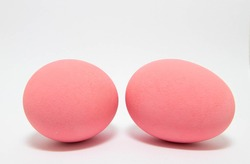 Photograph of two pale pink scrambled eggs against a white background.