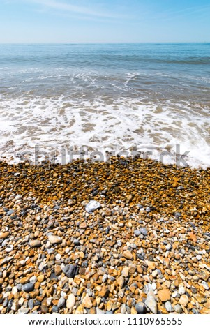 Photograph of waves breaking on the beautiful shingle beach at Seaford in Summer, Seaford, East Sussex, UK #1110965555