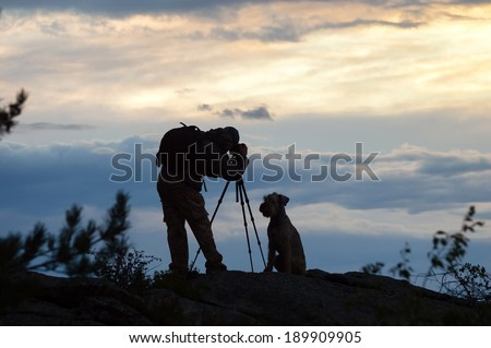 Photographer and dog silhouettes in the mountains at sunset