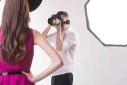 Photographer and model. Young man photographing fashion model holding hands on hip