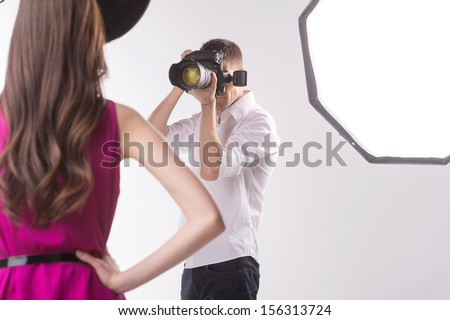 Photographer and model Young man photographing fashion model holding hands on hip