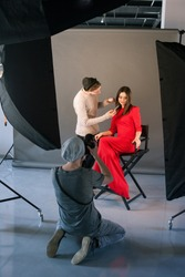 Photographer and stylist work in studio . Man taking shot of female model, visagist doing makeup. Creative team make commercials. Photo school, lookbook, fashion backstage concept