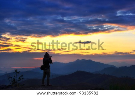 Photographer at mountain landscape at sun rise time - stock photo
