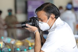 Photographer at work during Covid-19 pandemic. Photographer in mask and gloves shooting during lock down in India wearing N95 mask.
