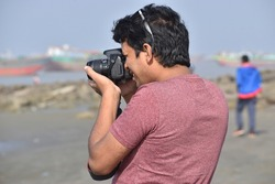 Photographer capturing beautiful scenery near sea beach. Professional photographer taking picture in a tourist spot