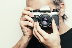 Photographer. Close up portrait of man holding vintage camera.