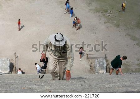 Photographer conquering main Chichen Itza pyramid, Mexico