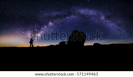 Photographer doing astro photography in a desert nightscape with milky way galaxy.  The background is stary celestial bodies in astronomy.  The heaven depicts science and the divine. #571149463