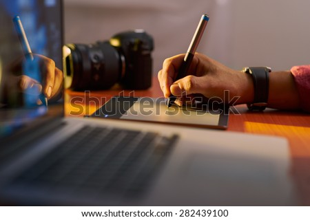 Photographer drawing and retouching image on laptop computer, using a digital tablet and stylus pen. Closeup of man\'s hand with dslr camera in background. Copy space in foreground