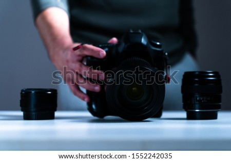 photographer equipment, cameras, lenses and hand reaching out to them #1552242035