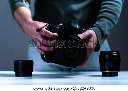 photographer equipment, cameras, lenses and hand reaching out to them #1552242038